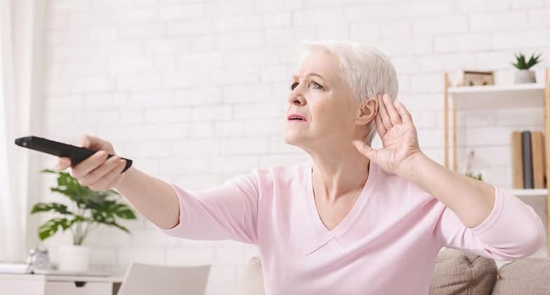 woman with hearing loss trying to hear the tv